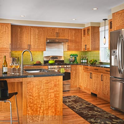 kitchen with cherry veneer over fiberboard cabinets, bronze pulls, soapstone countertops and green glass-tile backsplash