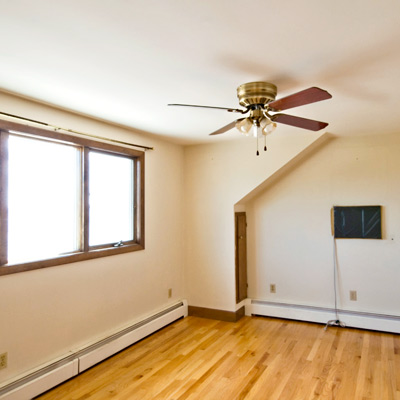 empty master bedroom with ceiling fan before remodel