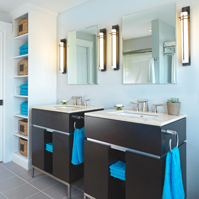 master bathroom with mirrored medicine cabinets, bronze finish light fixtures and his and hers vanities in dark wood