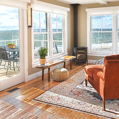 Cape Code living room with hardwood floors and views of waterfront