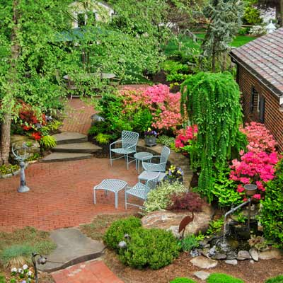 yard with brick gathering spots surrounded by stone walls, conifers and azaleas
