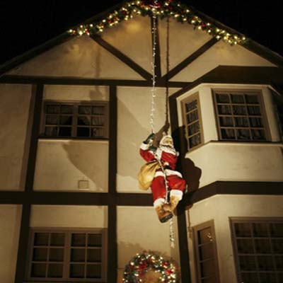 A figure of Santa scaling the side of a Tudor-style home