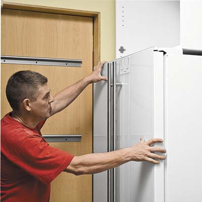 men lining cabinet fronts with fridge door