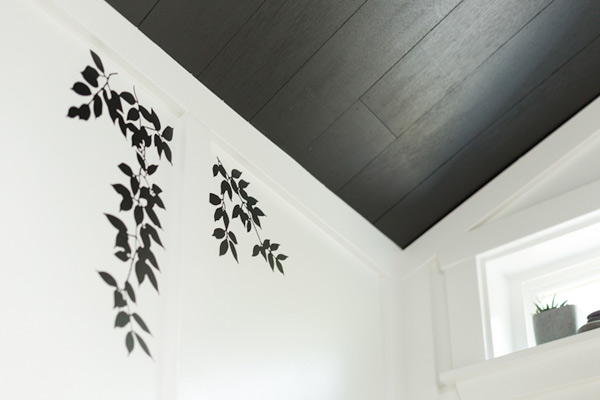 guest bath after redo with leafy decals on paneled walls