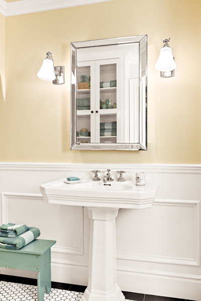 windowless, well-lit guest bathroom with white pedestal sink, medicine cabinet, vintage-look sconces after remodel