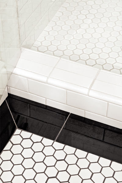 windowless, well-lit guest bathroom with hex and onyx tile floor after remodel