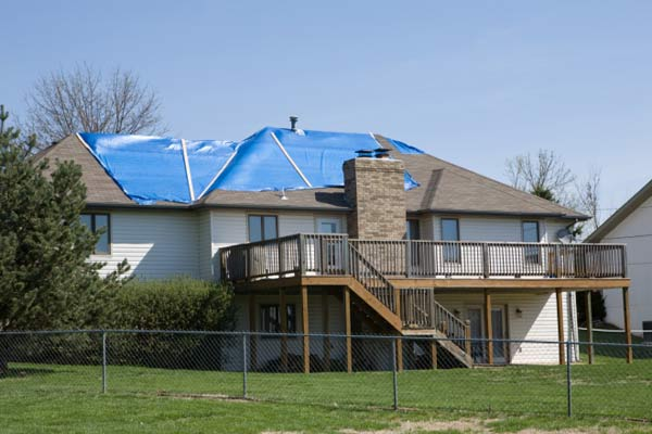 roof questions answered house with tarp on roof after weather damage