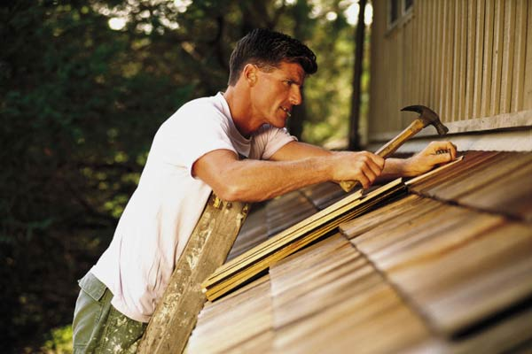 roof questions answered roof ridge vent man hammering onto roof addition against side of house