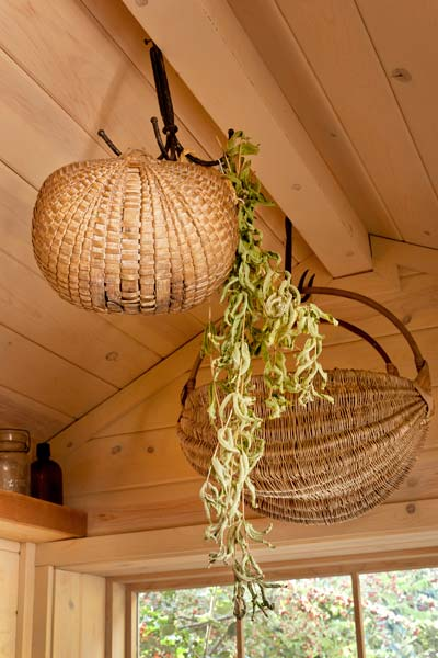 hooks used to dry herbs and hang baskets inside cottage style garden shed used as bonus room