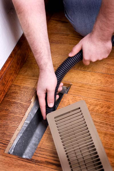 vacuuming vent register and grill for better heat circulation, fall easy upgrades for upkeep