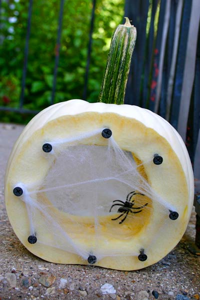 sliced open pumkin with fake cobweb and spider, painted pumkin carving alternative
