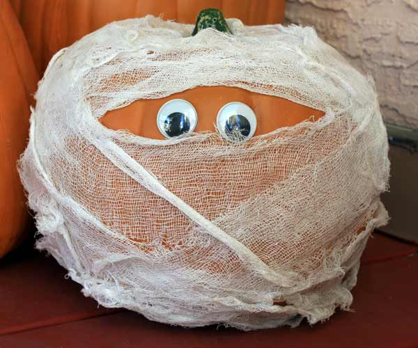 pumpkin wrapped with gauze to look like mummy, painted pumkin carving alternative