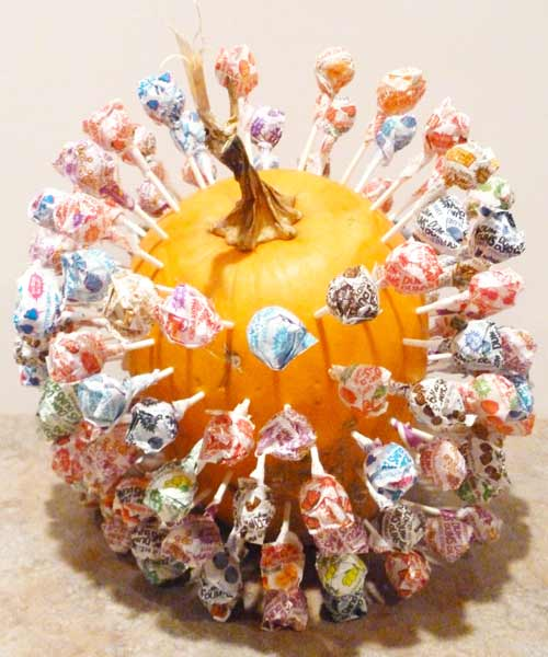 pumpkin with drilled holes used as lollipop holder, painted pumkin carving alternative