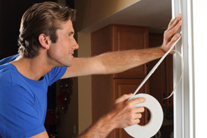 10 uses for weatherstripping man applying weatherstripping to a door