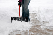 person shoveling snow in driveway or walkway