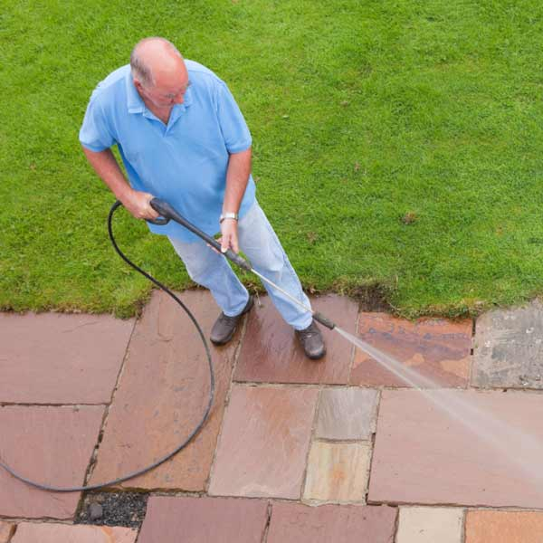 man power washing a walkway, homeowner survival skills