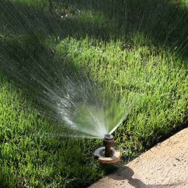 water sprinkler pointed toward the grass and away from the walkway and driveway surface