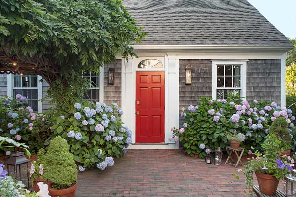 whole house remodel cape cod old restaurant house exterior with brick patio and hydrangeas