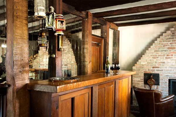 whole house remodel cape cod old restaurant house homemade bar with mirror back, chimney covered in salvaged bricks