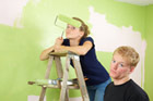 rival siblings painting a room