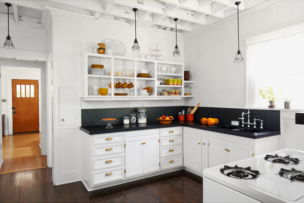 vintage look kitchen with dark wood floor, shaker style white cabinets, open shelving, exposed ceiling joists, reader budget remodel