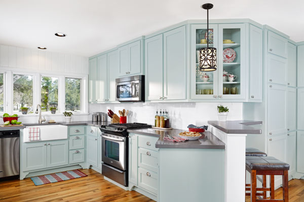 open kitchen after remodel with painted blue cabinets, angled quartz countertop
