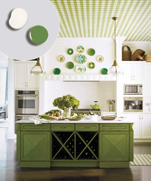 kitchen with green painted island, white painted kitchen cabinets, plates on display on wall, and printed green and white canvas covering ceiling, pendant lights