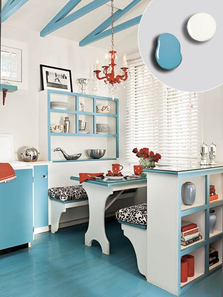 kitchen with exposed ceiling trusswork painted blue, white walls, blue painted cabinet doors and built banquette's edges, shelves