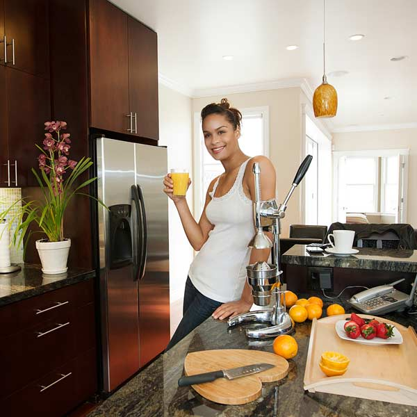 fit woman drinking fresh juice in kitchen