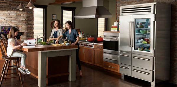 family in kitchen with glass-front refrigerator