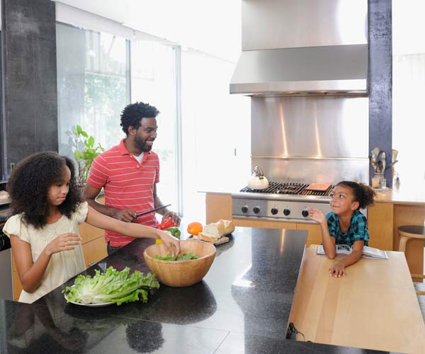 family prepping a meal in a large, open kitchen with an island