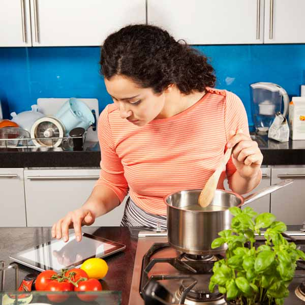 woman looking up healthy recipes on her iPad while cooking in kitchen