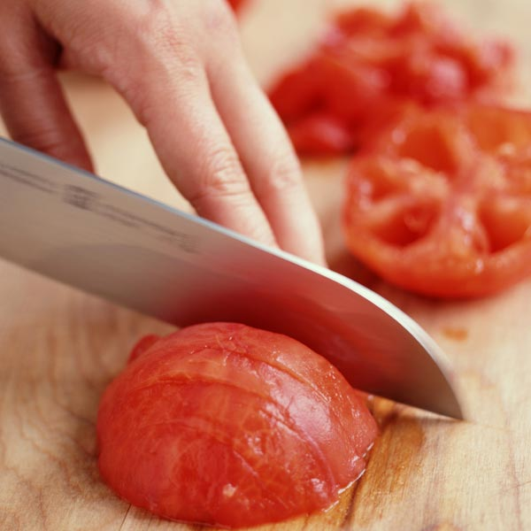 person slicing tomato with sharp knife