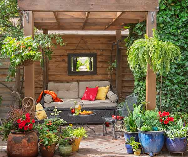 secret garden on urban plot wood pergola with daybed at brick patio, container plants