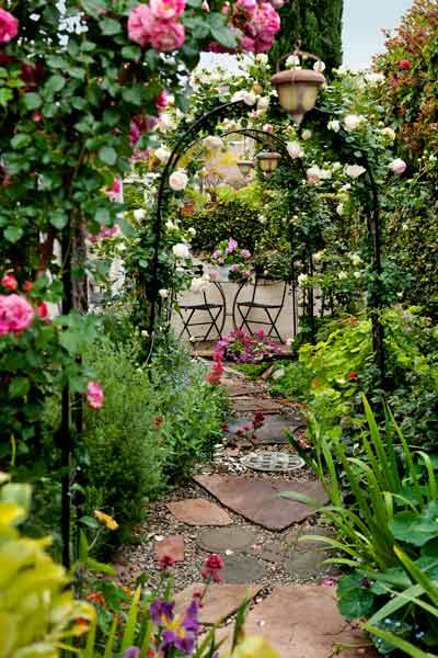 garden planning romantic gardens bistro set surrounded by flowers and rose-covered arbors