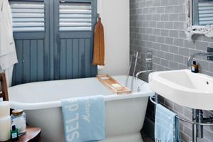 bath with soaking tub, salvaged shutters, tile wall and pebble stone floor, easy bath upgrades