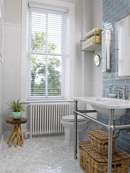 a console sink and train-style towel rack help open this this brighter and sleeker bath after remodel