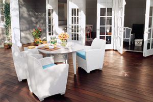 sunny hardwood deck with white deck chairs with aqua cushions set around a lively round table, with open french doors leading into the house behind