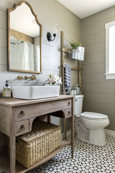 clean, bright bathroom with a desk vanity, mirror, wicker storage, cement tile, and sconce after a remodel