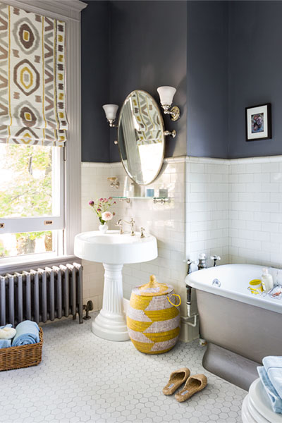 bright bathroom with white subway tile half-way up the wall and white, octagonal floor tiles. A porcelain tub sits to the right of a pedestal sink, with a yellow and white woven basket between. An oval mirror hangs between two sconces on the gray wall