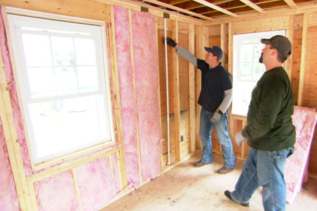 Kevin O'Connor helps install fiberglass insulation