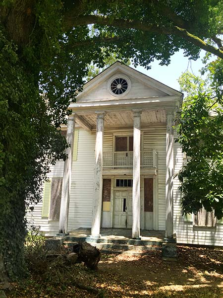 view of a distressed greek victorian home from the front, surrounded by overgrown trees. a round porthole window is set in the top above the pillars of the two-story porch