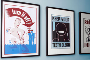 three framed WPA poster copies displayed on the blue wall of a bathroom, over white wainscotting and two blue bath towels hanging on a rod
