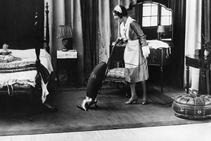 vintage photo of woman vacuuming a rug in a bedroom