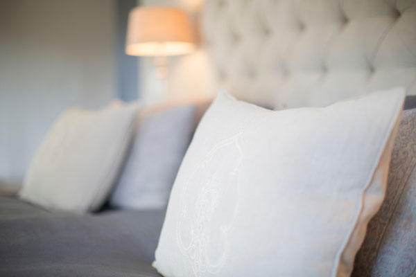 closeup of comfortable pillow on a wide bed, with a lit lamp in the background