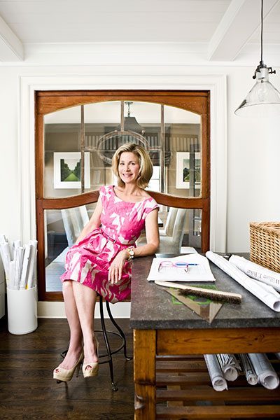 the interior designer and author Barbara Westbrook sits at a work table with open floor plans, in a white room with a large, wood-framed window behind her, exposing a dining room.