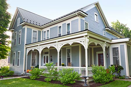 exterior of light gray folk victorian house with big wraparound porch with detailed white gingerbread style trim