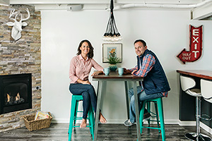 young couple sitting at bartop table in their newly finished basement with a wet bar and a fireplace with a faux taxidermy deer hanging in the background