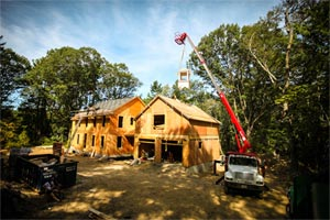 A boom truck lifts the pre-built cupola onto the framed roof of the North Shore house project garage, topping off a guest suite separated from the house.