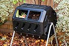 black plastic and metal frame turning composter in a yard